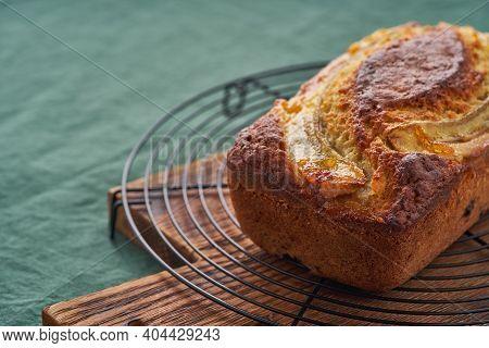 Banana Bread, Cake With Banana. Whole Loaf On Grid. Morning Breakfast With Tea On Green Linen Textil
