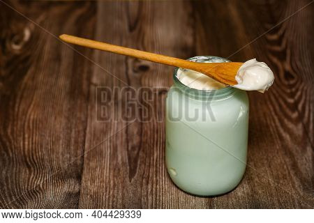 Homemade Milk Sour Cream In A Glass Jar With A Rustic Wooden Spoon. The Village Produces An Agricult