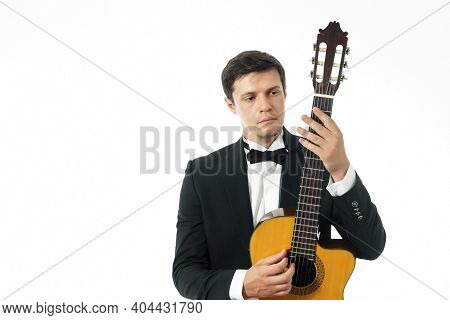 Young Man In Black Classic Suit Posing With Classical Guitar And Looking At The Neck Of A Classical