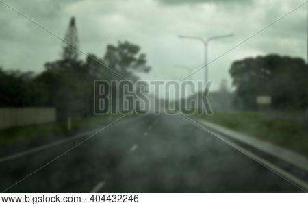A Blurred Scene Of Rain Falling On A Car Windscreen As It Travels Along A Suburban Road - Intentiona