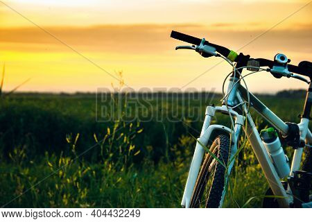 Close-up Of Mountain Bike Stands In The Rural Green Field At Summer Evening. Cycling Adventure And S