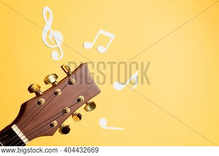 Musical Notes And Guitar Fretboard Close Up, Flat Lay On Yellow Background. Music Backdrop