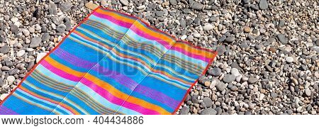 A Bright Colorful Rectangular Beach Mat In Blue, Orange, Turquoise, Pink Stripes Of Different Widths