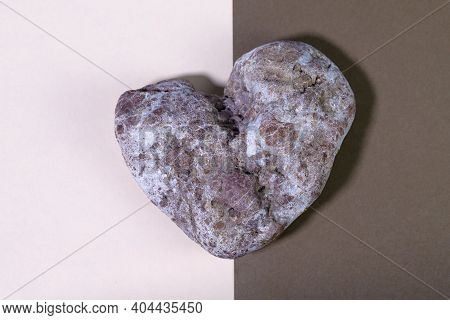 Colored Stone In The Shape Of A Heart On A Bright Two-tone Background. Stone Heart Close Up. Valenti