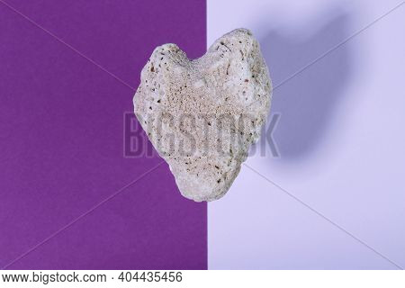 Levitation. Falling Heart-shaped Stone On A Bright Two-tone Background. Stone Heart Close Up. Valent