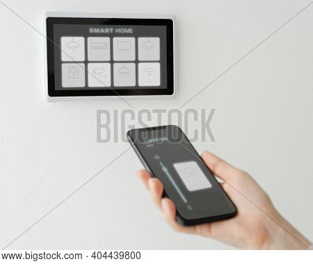 Woman using smart phone for home automation panel monitor