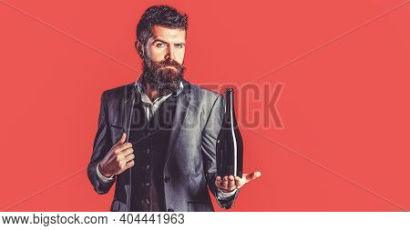 The Person Holds A Red Wine Bottle In A Hand. Man Holding Bottle With Champagne, Wine. Bearded Man W