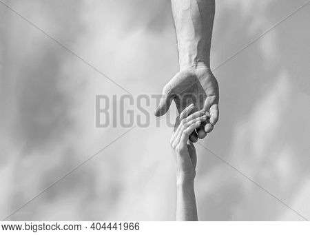 Hands Of Man And Woman On Blue Sky Background. Lending A Helping Hand. Hands Of Man And Woman Reachi