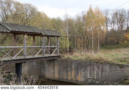 Wooden Footbridge With A Roof And Railings Across The River, Birch Trees With Yellow Leaves, Autumn,