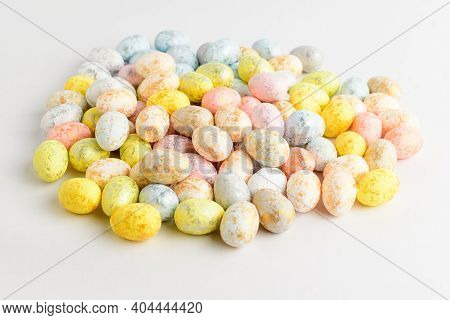 Heap Of Mixed Chocolate Coated Easter Eggs Candies Isolated On A White Table, Tasty Sugary Dessert F