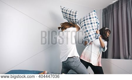 Happy Young Couple Having Pillows Fight In The Bedroom. Love And Affection Concept. High Quality Pho