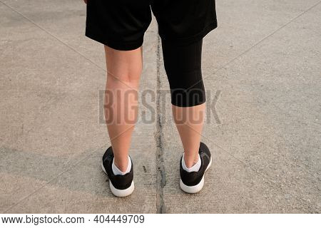 Back Side Of Runner Woman Wearing Knee Support To Prevent And Reduce Knee Pain From Running. This He