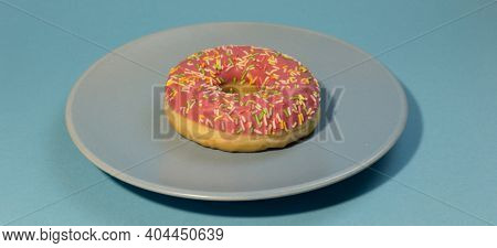 Pink Doughnut Or Donut With Colored Sprinkles On A Blue Background. Bitten Off American Bagel.