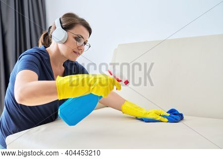 Woman Doing House Cleaning, Female In Headphones And Gloves With Detergent Washing Furniture In Room