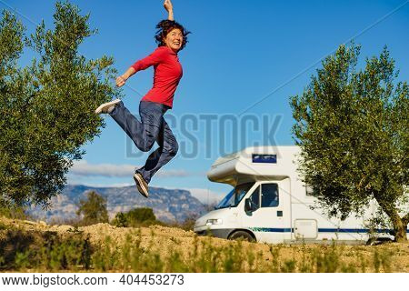 Woman Enjoying Trip With Motor Home, Jumping In The Air Against Camper Car And Spanish Mountains Nat