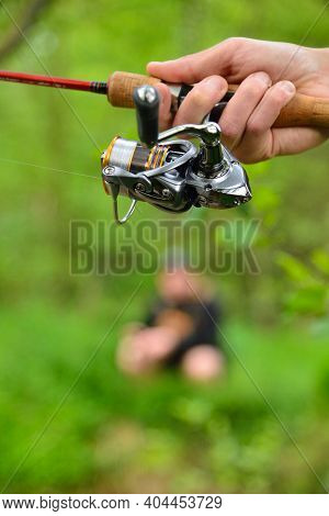 Fishing Reel On Rod In Fisherman's Hand On Green Background With Defocused Fisherman In Background