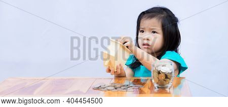 Asian Girl Takes Coin From Piggy Bank In Wooden House. Children Use Coins That Are Saved To Buy What