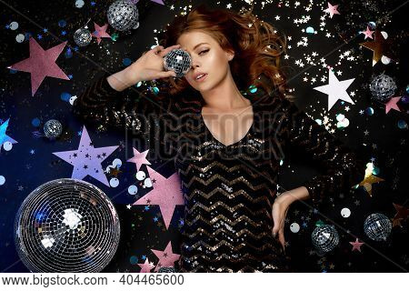 Glamour Model Posing On The Floor. Gorgeous Curly Blonde Woman In A Black Sequins Dress For Party Ho