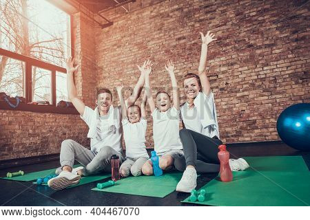 Dad Helps His Son Do Stretching On The Mat In The Gym. Mom And Dad Help Their Children Do Full Body