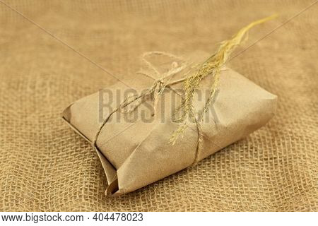 Simple Eco Friendly Gift Box Package Wrap With Brown Paper. Burlap Background. Delivery Of Ecologica