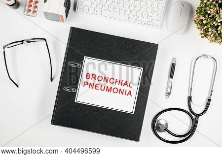 Doctor's Workspace, In The Center Is A Folder With The Inscription: Bronchial Pneumonia