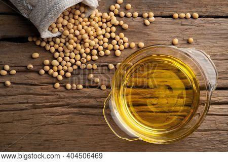 Soybean Oil In Glass Bowl With Soybean On Wooden Table.top View.