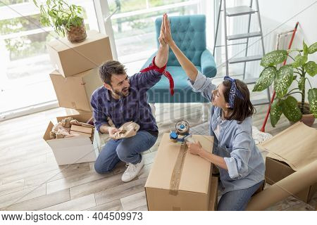 Beautiful Young Couple In Love Doing High Five After Packing Things In Cardboard Boxes, Getting Read