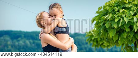 Mother Embracing Her Daughter Wearing Sportswear Outdoors. Woman And Child Embracing Outdoor
