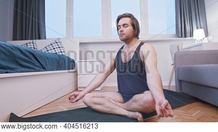 Young Calm Man Meditating In His Bedroom. Wellbeing Concept. High Quality Photo