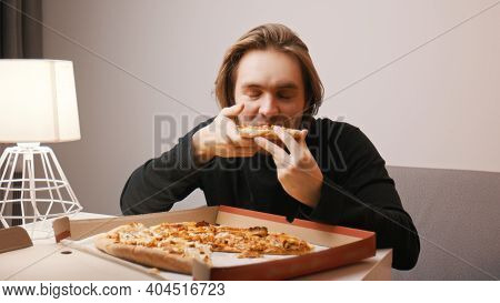 Young Caucasian Man Eating Pizza And Smiling. High Quality Photo