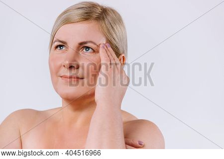 The Older Woman Frowns Upward And Is Unhappy With The Wrinkles On Her Face. White Background. Enlarg
