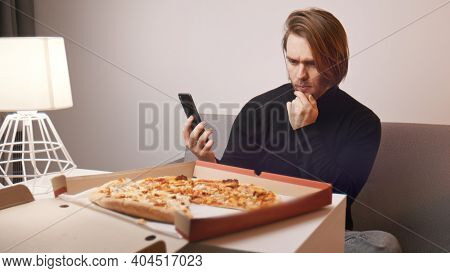 Young Caucasian Man Having A Complaint About Pizza. Holding Smartphone To Call Customer Support. Hig