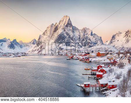 Astonishing Evening Cityscape Of Reine Town. Red Rorbuers On The Shore Of Reinefjorden. Popular Trav