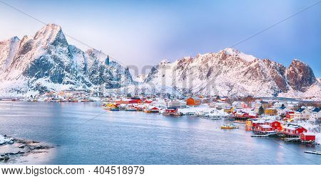 Dramatic Evening Cityscape Of Reine Town. Red Rorbuers On The Shore Of Reinefjorden. Popular Travel