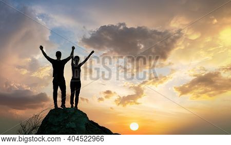 Man And Woman Hikers Standing On A Big Stone At Sunset In Mountains. Couple Raising Up Hands On High