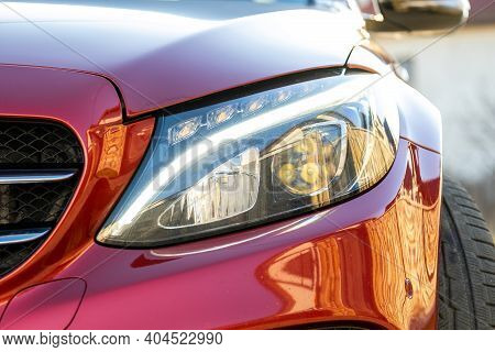 Closeup Of Front Headlight Of New Clean Car Parked On A City Street Side.