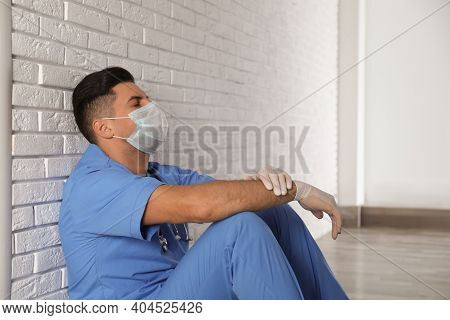 Sad Doctor Sitting Near White Brick Wall Indoors. Stress Of Health Care Workers During Coronavirus P