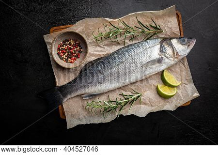 Raw Seabass Fish With Rosemary And On Dark Background, Top View