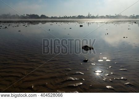 Many Giant Tidal Pools In A Wadden Sea At Low Tide With The Shore In The Background