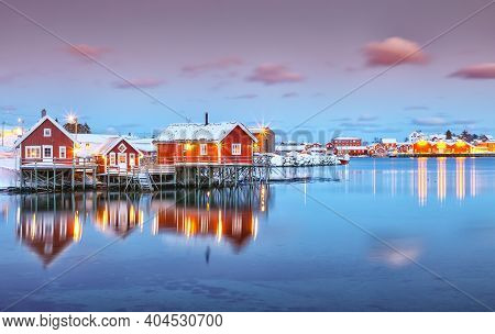 Dramatic Evening Cityscape Of Reine Town. Red Rorbuers On The Shoore Of Reinefjorden. Popular Travel