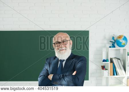 Teacher In The Classroom Near The Blackboard Is Teaching A Lesson. Professor At The University Is Gi