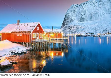 Amazing Night Cityscape Of Reine Town With Snowy Moutaines On Background . Popular Travel Destinatio