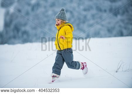 Child Running On Snow In Winter. Kids Playing And Jumping In Snowy Forest. A Kid Runs Through The Sn