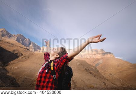 Young Happy Woman In A T-shirt And Jeans Stands High In The Mountains With Her Arms Outstretched Enj
