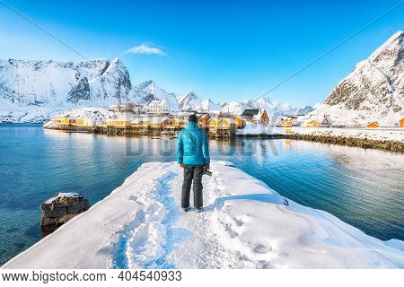 Tourist Admire The View Of The Sakrisoy Village And Snowy Mountaines On Background. Popular Tourist