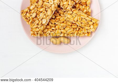 Peanut Brittle Candies In Honey Caramel On Plate On White Background