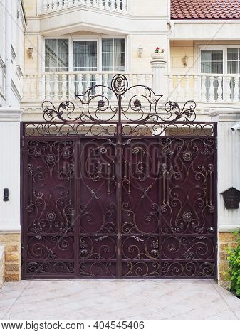 An Iron Burgundy Fence With A Wrought Gilded Pattern Stands In Front Of The House In Marble