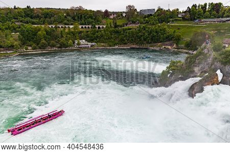 Rhine Falls, Switzerland - May 6, 2017: The Rhine Falls At Cloudy Day, Tourist Boat With Passengers