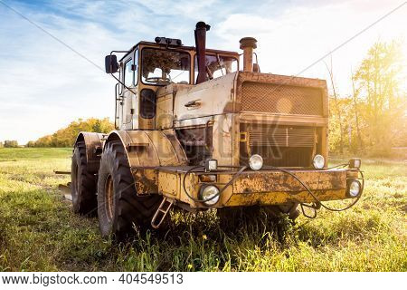 Heavy Duty Wheeled Tractor On An Agricultural Field In The Rays Of The Autumn Sun