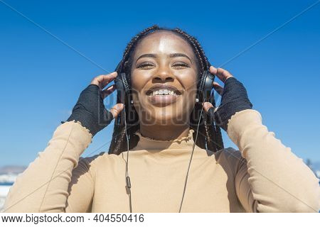 Closeup Portrait Of Young Black Afro Girl Smiling With Headphones And Blue Sky Background, Pretty Af